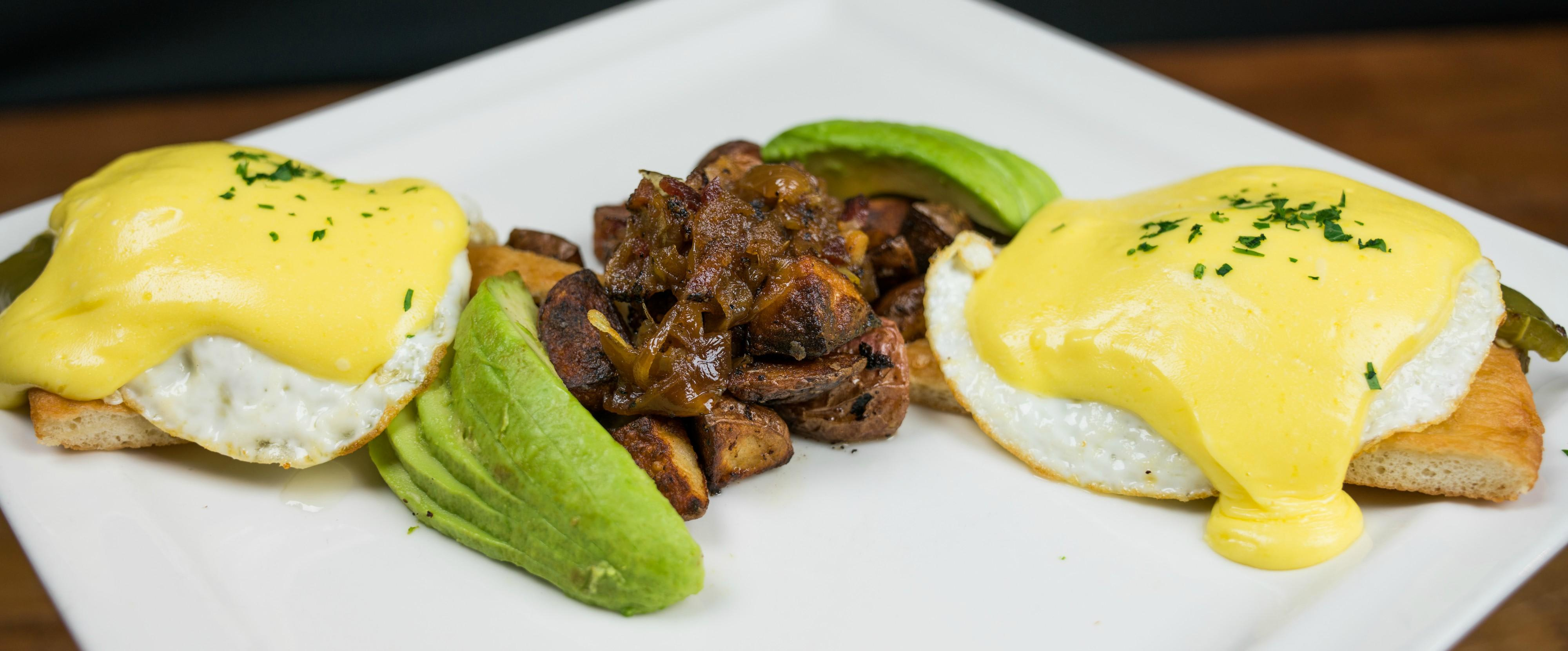 TB&G Benedict Poached eggs, jalapeño bacon, roasted green chilies, and avocado, served on Indian fry bread with hollandaise, roasted potatoes with bacon and caramelized onions at Tonto Bar & Grill
