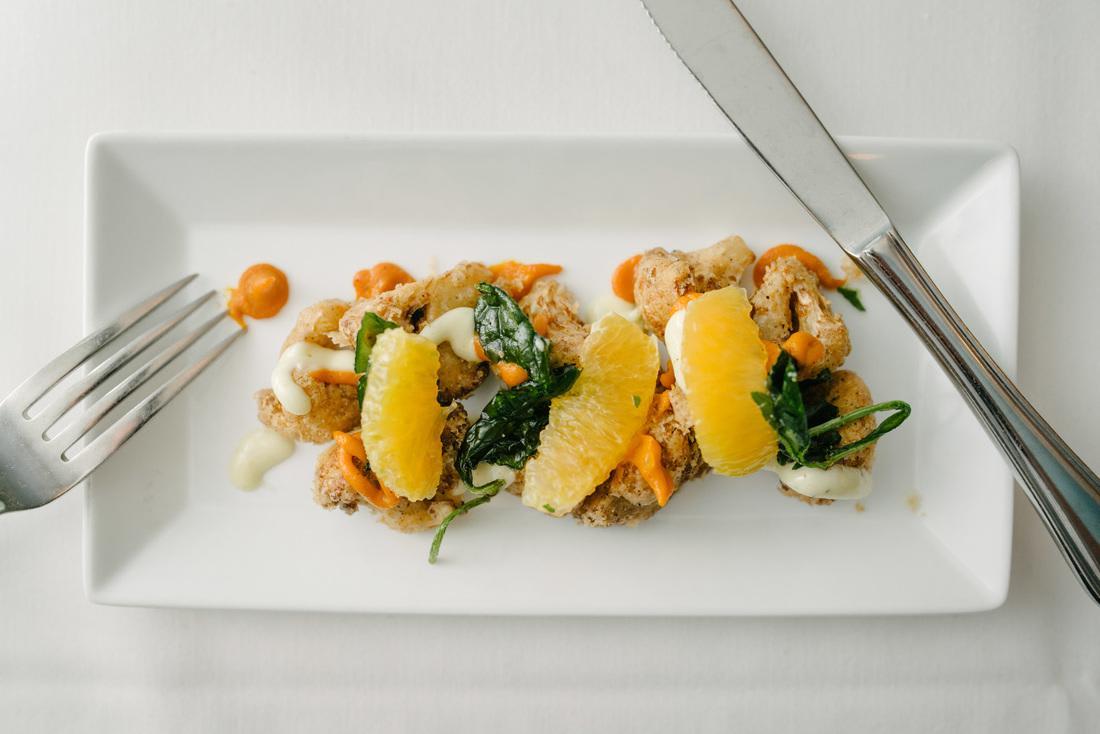 lightly breaded cauliflower, crisp broccoli rabe leaves, orange segments, capers, lemon and carrot aioli at Zingari Ristorante