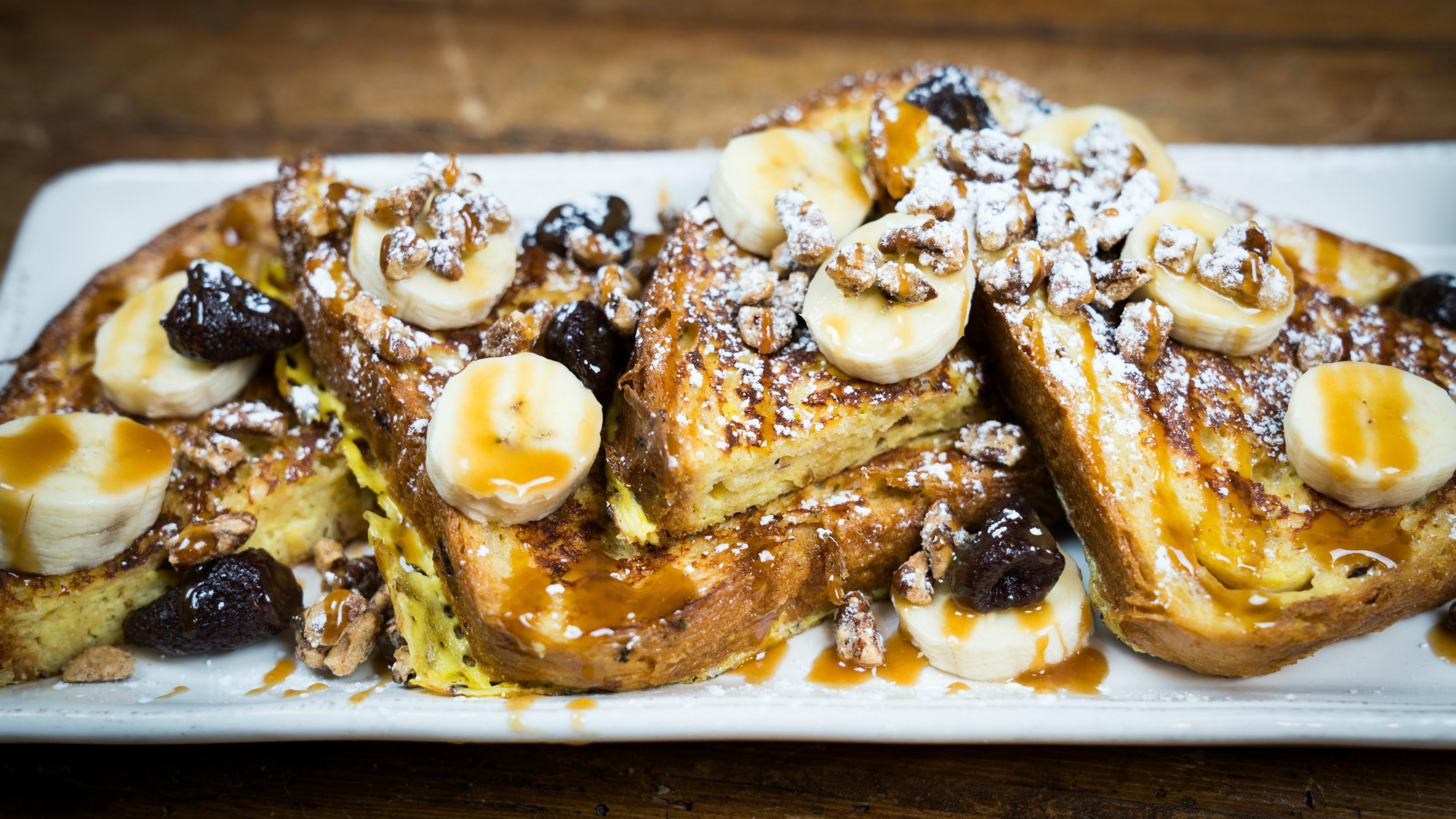 French Toast House-baked cinnamon raisin brioche with caramelized bananas, candied pecans, sun-dried strawberries, bourbon maple syrup at Tonto Bar & Grill