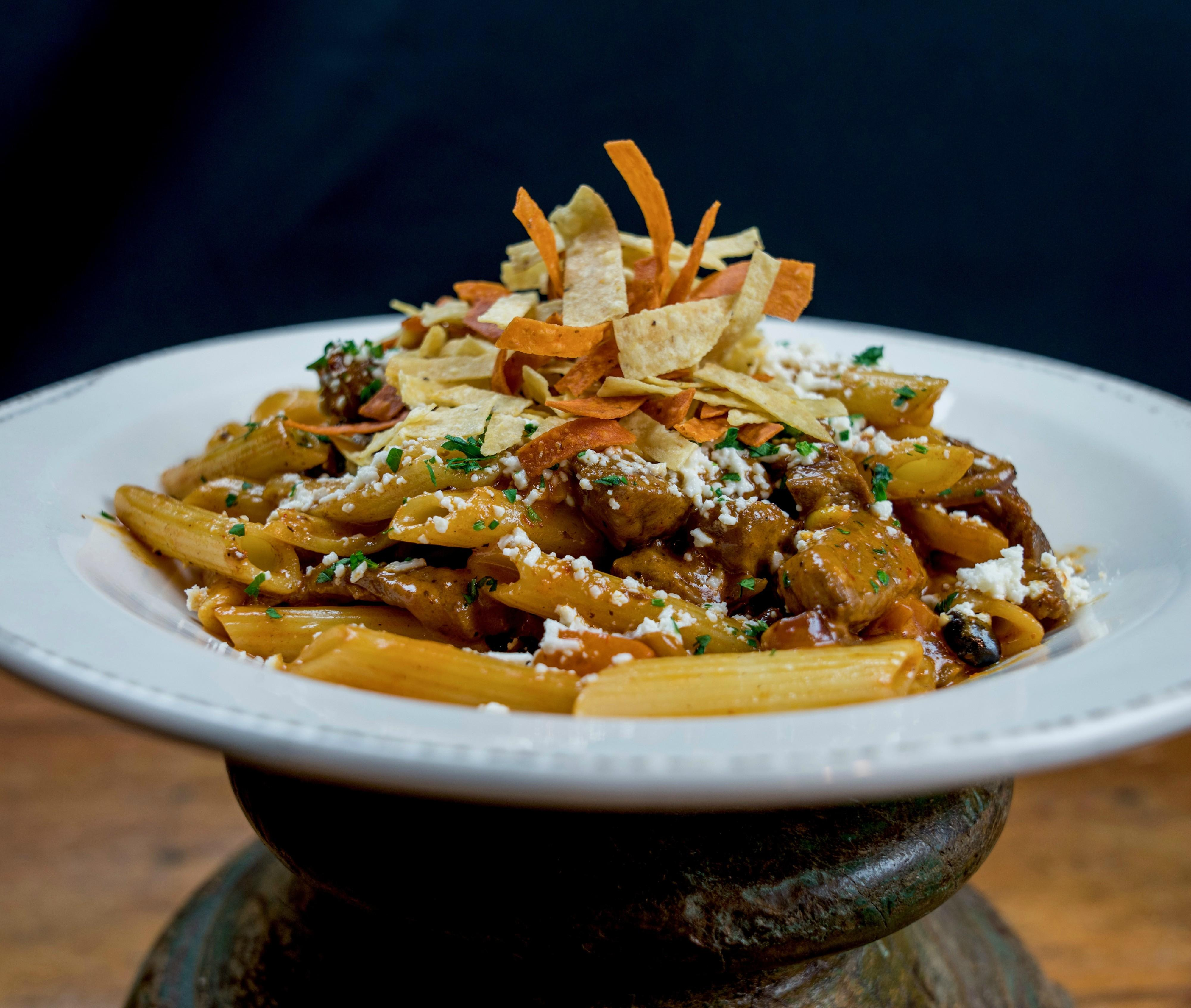 Penne Pasta Beef tenderloin tips, black beans, corn, tomatoes, red onions, mild red chili sauce & feta cheese at Tonto Bar & Grill
