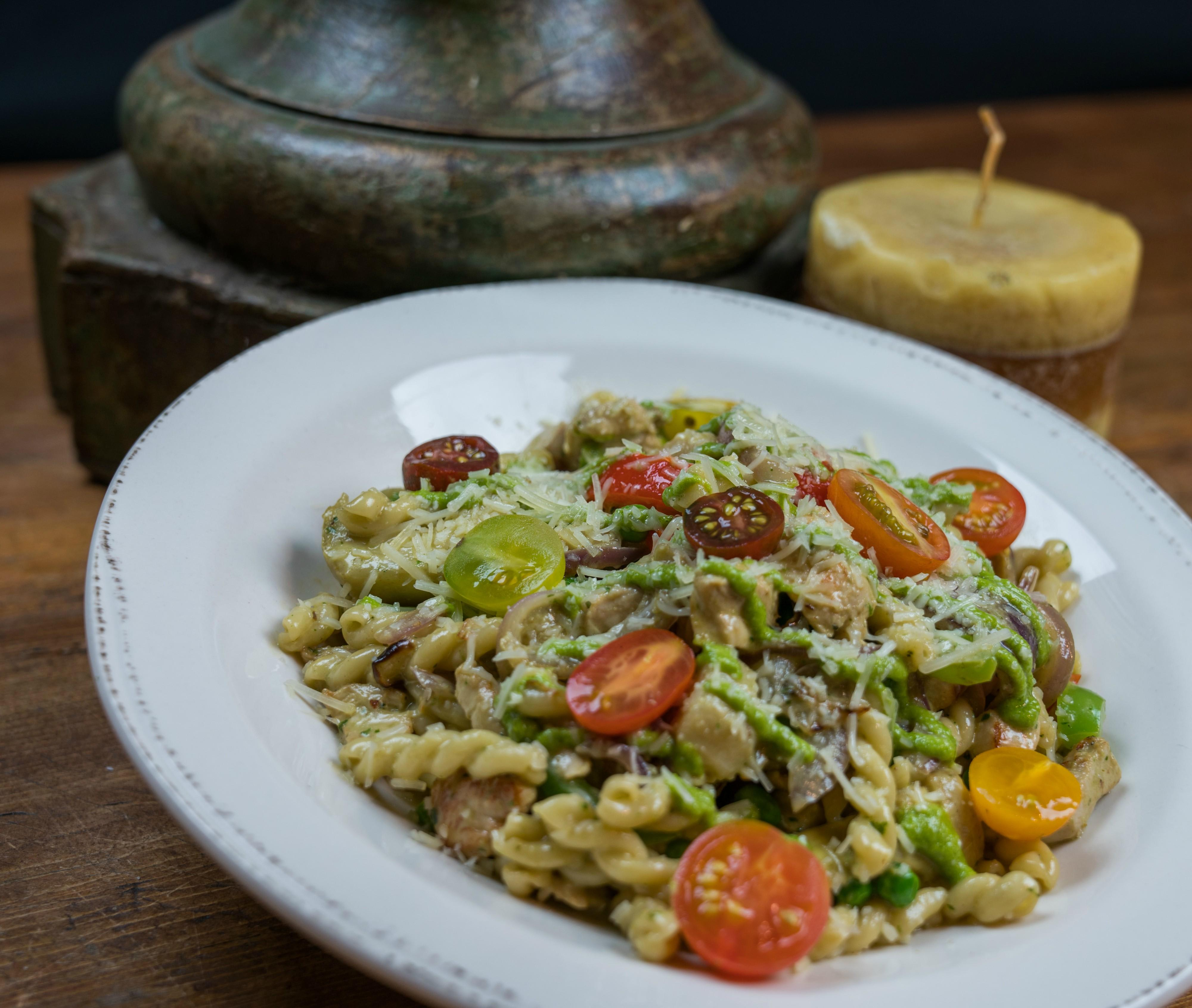 Gemelli Pasta Garlic chicken, artichokes, red onions, peppers, peas, heirloom tomatoes, basil cream & fresh pesto at Tonto Bar & Grill