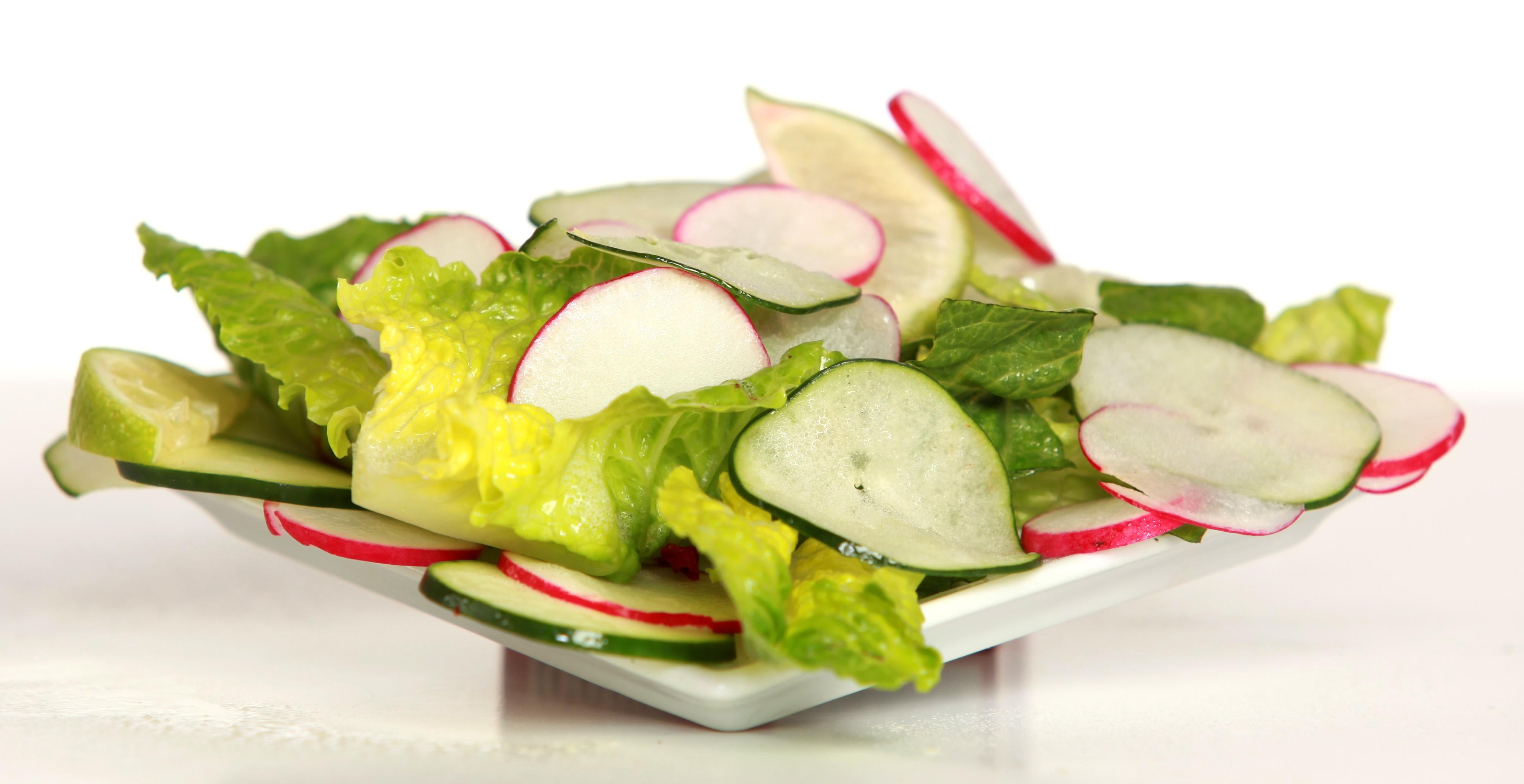 Fresh made Bombay Salad is a medley of romaine lettuce, chickpeas, diced tomatoes, sliced radish and cucumbers served with our house made spiced lime vinaigrette. at Bombay Wraps