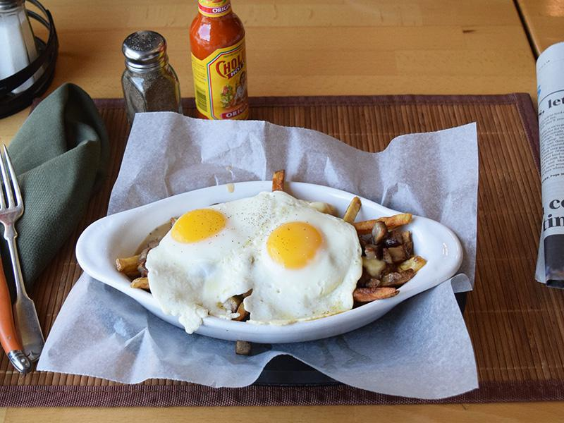 Breakfast Poutine - Fries, cheese curds, sausage, and beef gravy topped with two eggs your way at West Allis Cheese & Sausage Shoppe